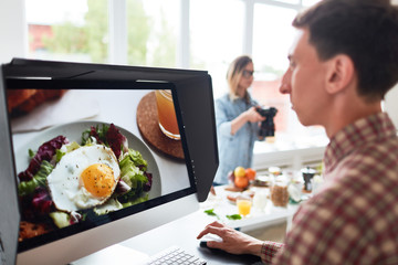 Profile view of concentrated young food designer sitting in front of computer monitor and retouching photos, his female colleague taking pictures of appetizing breakfast