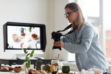 Profile view of concentrated young food photographer taking picture of served table for healthy breakfast, spacious production studio on background