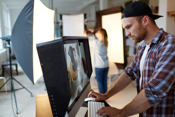 Profile view of young handsome food designer retouching photo while standing in front of modern computer, interior of production studio on background