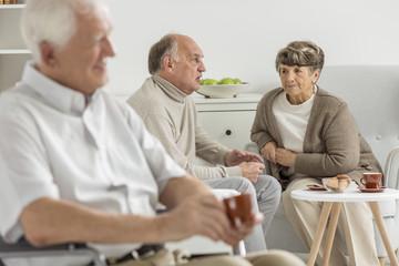 Elder people sits on chairs