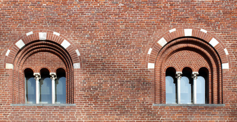 Two mullioned windows with three lights on a brick wall