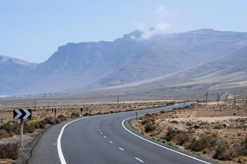 Asphalt road in a desert with mountains