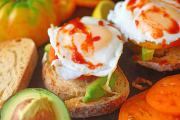 Fried eggs topped with hot chili sauce on avocado toast