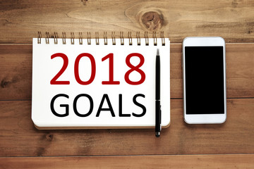 2018 goals on paper note book background and smart phone on wood table, business and new year concept