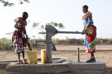 Samburu tribal women collecting fresh water from well in desert landscape. Kenya, Africa.