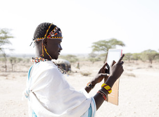 Samburu Warrior using tablet. kenya, Africa.