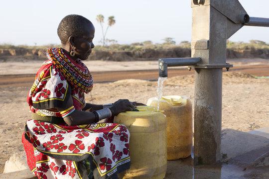 Samburu tribal woman collecting fresh water from borehole  in desert landscape. Kenya, Africa.