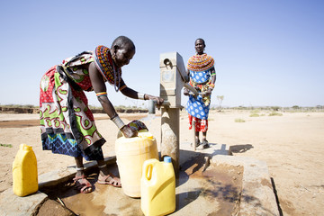Women from Samburu tribe collecting fresh water from borehole in desert. Kenya, Africa