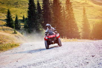 Couple enjoying driving quad bike on mountain road