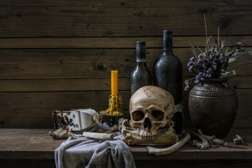 Human skull and pile bone with candle Light, Still life style on  wooden table