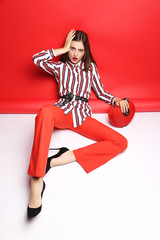 Fashion portrait of beautiful young woman. Red pants, red handbag, blouse, red background