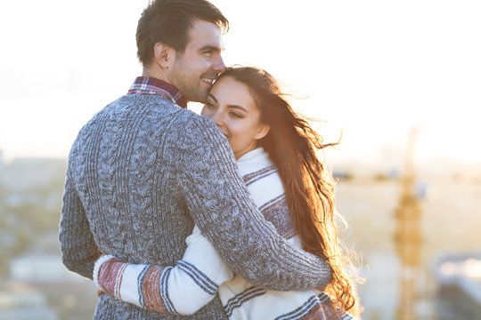 Young man and woman embrace and having fun outdoors