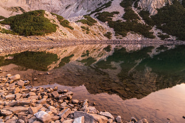 Poster Reflexion Peak Sinanica reflected in the water of the lake at sunset