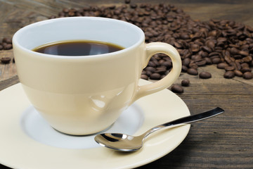 Black coffee in cream colored cup with silver spoon, In the background fresh roasted coffee beans on a weathered wooden table.