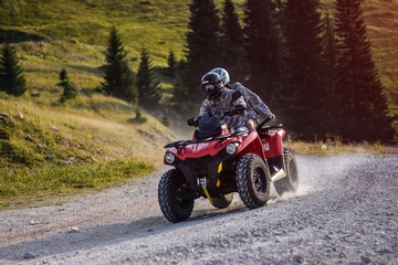 People driving quad bike on mountain road
