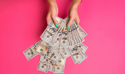 A woman is holding money in her hands. Pink background. Top view copy space.