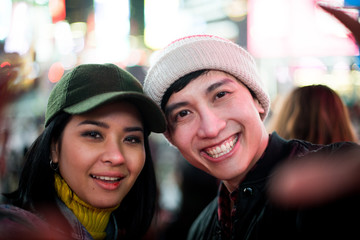 Happy couple taking selfies on Times Square