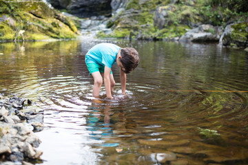 The boy is standing in the water