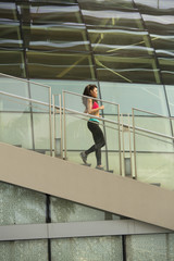Young asian woman running down the stairs