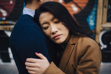 Asian lovers on vacation in Madrid in winter wear