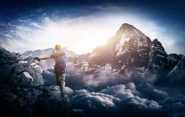 Bergsteiger an Klettersteig blickt auf fernen Berggipfel am Horizont