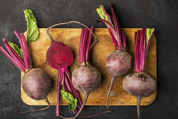 Raw organic farm beetroot on a vintage wooden cutting board on a plain black background. Top View.