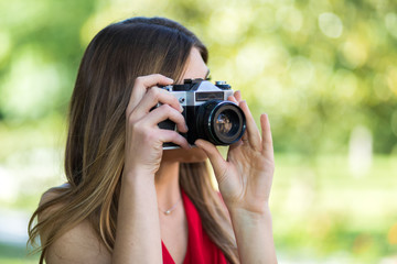 Young woman taking pics outdoor with her camera