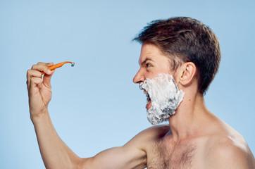 man in shaving foam holds a razor, scream, emotions, portrait