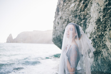 Beautiful brunette girl bride in a grey gown of lace and tulle, covered her face with a veil, hand on breast, profile, horizontal, sea, waves, summer