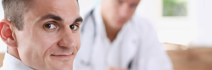 Satisfied happy handsome smiling male patient with doctor