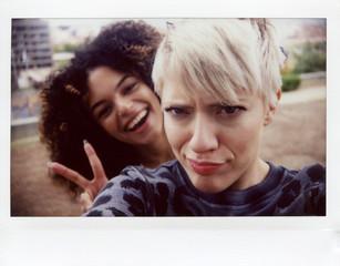Selfie of two joyful girlfriends made on
