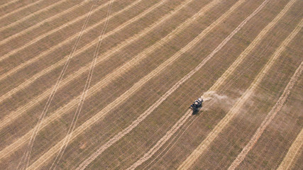 Drone shot of tractor working on hay field.