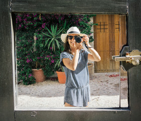 Woman with hat taking a selfie in a mirror