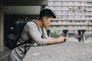 A Malaysian man leaning on a concrete ledge, using his mobile phone