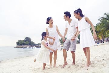 Happy family of four strolling on Sentosa beach
