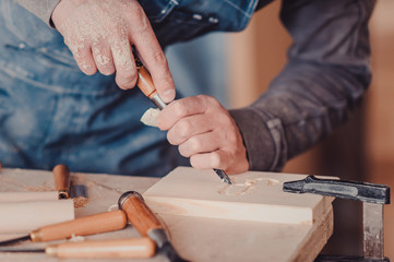 carpenter use a chisel to shapes a wooden plank.