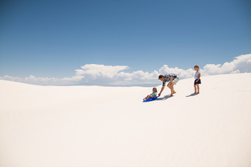 Father pushes daughter on sled down sand hill in White Sands National Monument