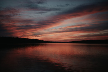 A dramatic red sky sunset over a calm lake