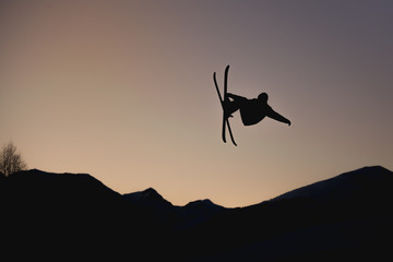 Silhouette of Skier in Mid-air, from the big jump freestyle at sunset