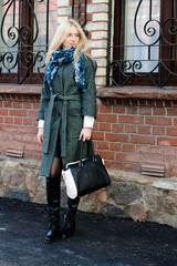 Девушка со светлыми волосами стоит на улице в сером пальто и шарфе, в руках держит сумку