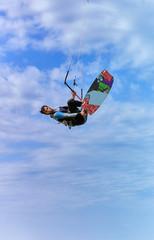 Kitesurfing on waves at sea in summer.