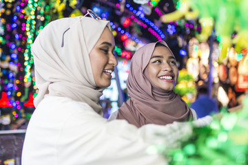 Two muslim ladies shopping for Hari Raya lights and decorations.