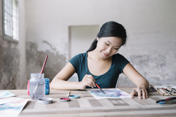 Smiling vietnamese painter drawing with pencil