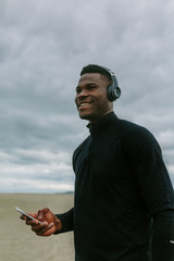 Smiling Young Man Using His Phone and Listening Music Doing Sport
