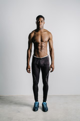 athletic topless man in pants and sneakers
