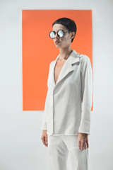 Fashion/conceptual portrait of female model on white adn orange background.