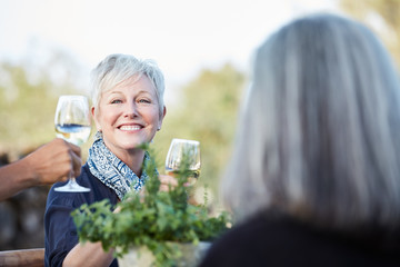Portrait of Senior woman with group of friends enjoying a farm to table dinner party