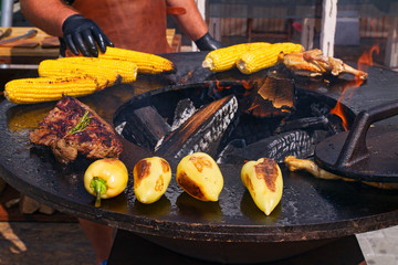 Man preparing barbecue outdoors. Cooking of grilled beef, chicken, corn and vegetables on open kitchen international food festival, event of street food