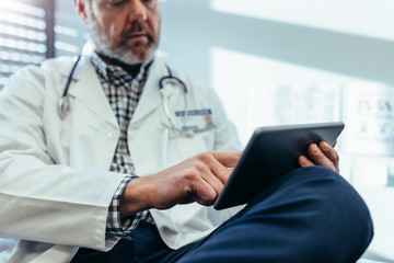 Doctor using digital tablet in his office