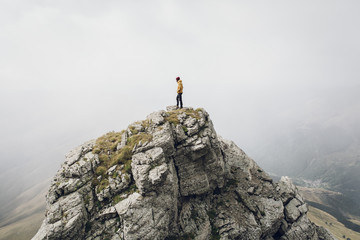 Young man on top of a rocky mountain foggy around